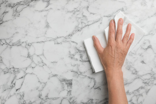 Woman wiping marble table with paper towel, top view. Space for text