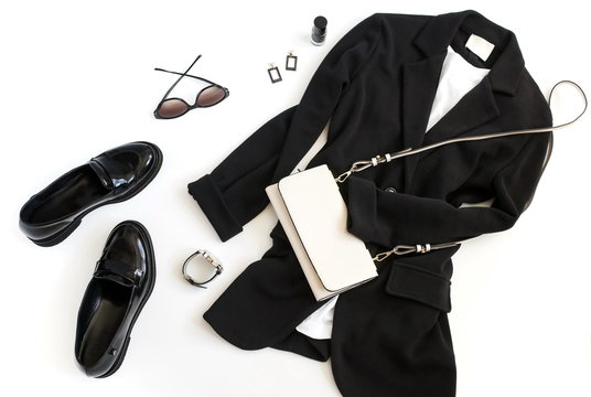 Women fashion clothes and accessories top view background. Flat lay female autumn style look with  black blazer , shoes loafer, bag, sunglasses, accessories on white background. Copy space.