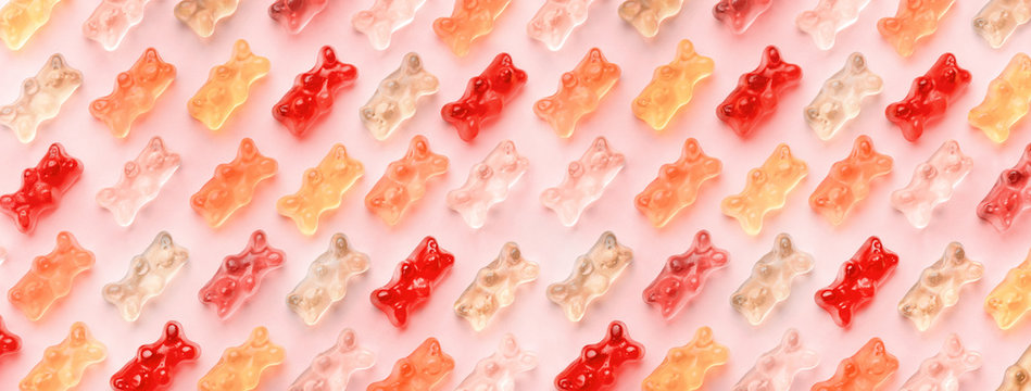 Flat lay composition with delicious jelly bears, jelly bears pattern on pink background, panoramic image