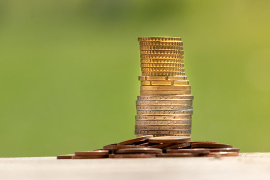 Coin on wooden table in front of green bokeh background. There is light flare on the right. Coins stacked coins on the table.