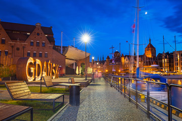 Beautiful architecture of Gdansk with an outdoor sign at dusk, Poland