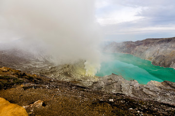 Acrylic Prints Coral Crater of a volcano with a green sulfuric volcanic lake and volcanic smoke. View of the smoking volcano Kawah Ijen in Indonesia. Mountain landscape