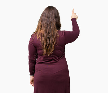 Beautiful and attractive plus size young woman wearing a dress over isolated background Posing backwards pointing behind with finger hand