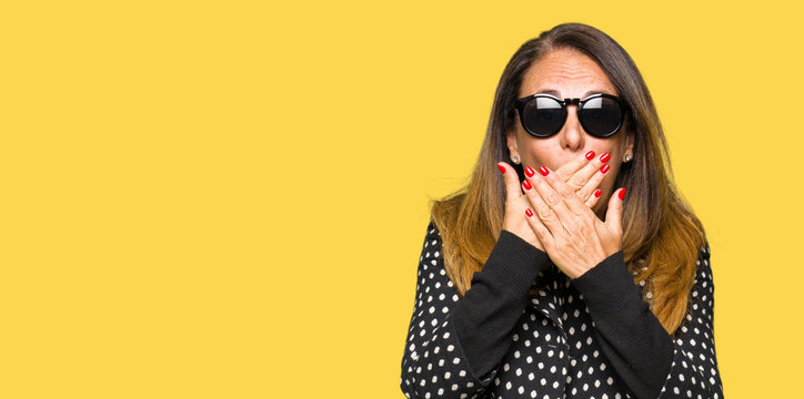 Beautiful middle age woman wearing sunglasses shocked covering mouth with hands for mistake. Secret concept.