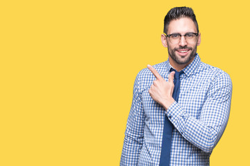Young business man wearing glasses over isolated background cheerful with a smile of face pointing with hand and finger up to the side with happy and natural expression on face