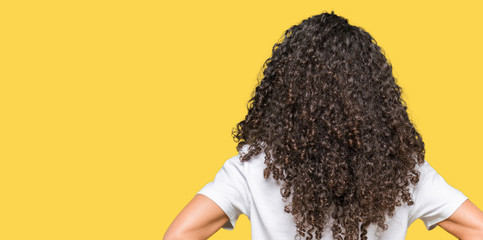 Young beautiful woman with curly hair wearing white t-shirt standing backwards looking away with arms on body Wall mural