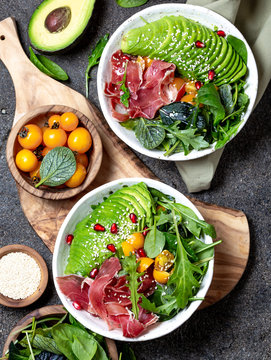 Low carbs bowl. Fresh salad with green spinach, rucola, avocado an ham serrano in white bowl, gray background, top view