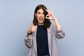 Young woman over isolated blue wall showing ok sign and thumb up gesture