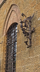 Torch stand with dragon as a city symbol, a detail from medieval building in Voltera, Tuscany, Italy