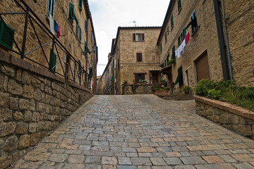 Steep cobblestone street surrounded by vintage stone buildings in Voltera, Tuscany, Italy