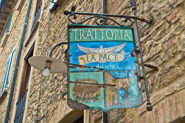 Entrance to very old trattoria in medieval building, a detail from the streets from Voltera, Tuscany, Italy