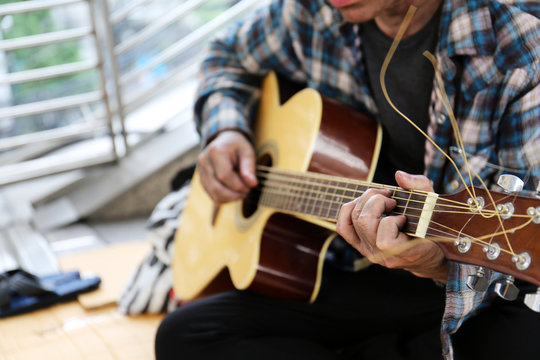 Close-up hand of homeless man playing acoustic guitar on walking street.