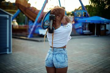 Girl holding skateboard in summer