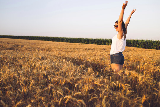Beautiful Young Woman Happy with arms raised in field