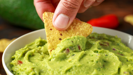 Man hand is picking some guacamole dip with nachos chip. Healthy Vegan, Vegetables food.