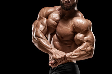 Muscular man showing muscles and biceps isolated on the black background. Bodybuilder male naked torso abs