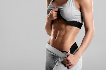 Fitness woman showing abs and flat belly, isolated. Athletic girl shaped abdominal