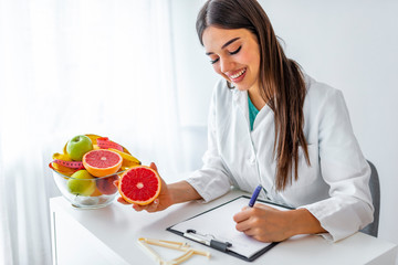 Portrait of young smiling female nutritionist in the consultation room. Nutritionist desk with healthy fruit, juice and measuring tape. Dietitian working on diet plan.
