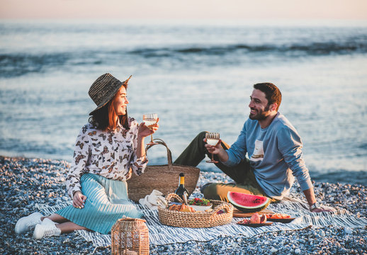 Summer beach picnic at sunset. Young happy couple having weekend picnic outdoors at seaside with bottle of sparkling wine, fresh fruit and tray of tasty appetizers, drinking wine and smiling