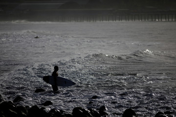 A surfer gets in the water at Punta Roca Beach in La Libertad