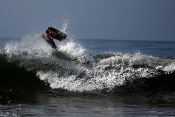 A surfer rides a wave in a body board at Punta Roca Beach in La Libertad