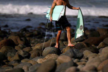 A surfer walks out of the water with a broken surfboard at Punta Roca Beach in La Libertad