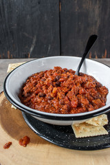 warm bowl of chili and beans with crackers in rustic setting