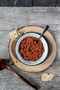 warm bowl of chili and beans with crackers in rustic setting flat lay