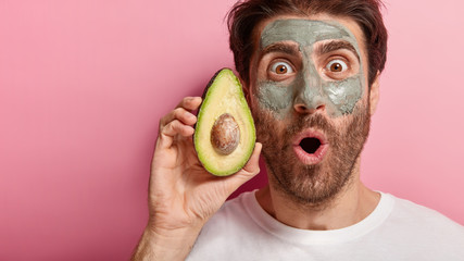 Spa and beauty concept. Cropped image of handsome man stares with widely opened eyes at camera, applies natural clay mask on face, holds slice of avocado, visits spa salon, isolated on pink wall