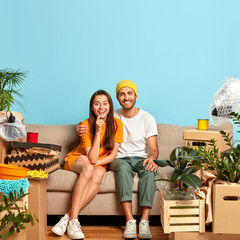 Start new family. Glad young couple in love embrace on couch, happy to buy new house, begin living together, plan to make modern repairing, many boxes with personal belongings around, blue wall