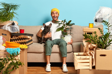 Image of positive fashionable guy rents new flat, lives together with favourite dog, sits on couch, holds houseplant, rejoices cheap loan has many personal stuff and household things. Mortgage concept