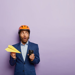 Industrial male engineer looks with stupefaction up, holds paper airplane, takeaway coffee, wears protective helmet and blue classy suit, has embarrased gaze, poses against purple background