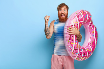 Yeah, finally summer! Joyful foxy holidaymaker clenches fist, rejoices coming holiday, dressed in casual outfit, carries inflated donut ring, shouts from pleasure, wins ticket for tour abroad