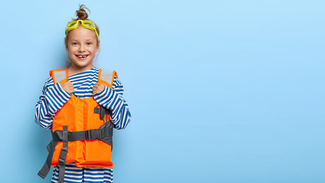Happy little female kid wears goggles and lifevest, plays on beach, has good vacation, dressed in striped sweater, stands against blue background, blank space for your information. Summer holiday