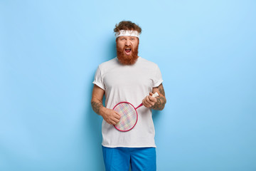 Active leisure concept. Funny determined red haired tennis player holds racket, pretends playing guitar, wears sport outfit, has fun on court, isolated on blue background. Sport and entertainment.