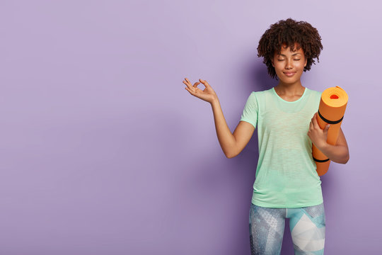 Young relaxed dark skinned woman practices yoga, meditates indoor for feeling relaxation, has eyes closed, holds fitness mat, dressed in active wear, isolated on purple background blank space on left