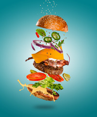 Tasty cheeseburger with flying ingredients on color pastel background. High resolution image.