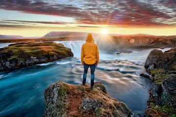 Fototapeta Man standing by amazing Godafoss waterfall in Iceland during sunset, Europe obraz