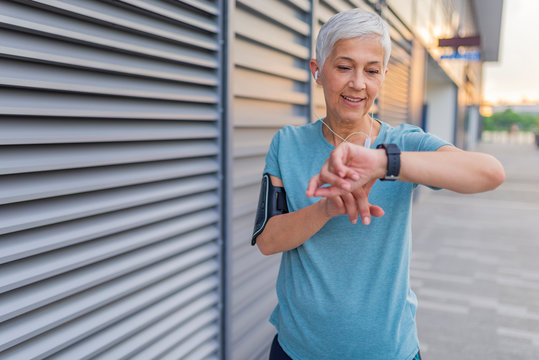 Checking the pulse. Athletic mature woman monitoring her running performance on smartwatch. How long was that? Senior woman setting up the fitness smart watch for running and checking watch device