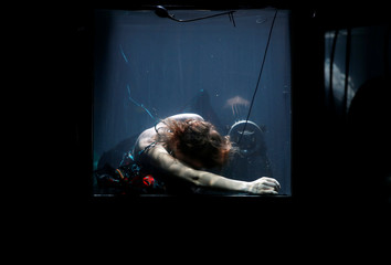 "Danish musician Nanna Bech performs underwater in a glass water tank during ""AquaSonic"", a submerged musical performance, at the Malta International Arts Festival in Valletta"