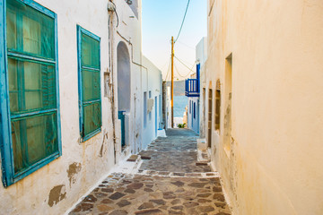 Street view of Adamas village with paved alleys and traditional cycladic architecture in Milos...