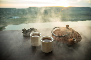 Tea concept. Japanese tea ceremony culture east beverage. Teapot and cups on table with bamboo leaves on sunset