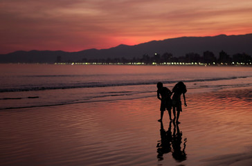 Children walk on a beach during sunset in Praia Grande