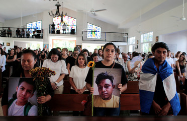Relatives and friends hold pictures of Gerald Vasquez and Francisco Flores during a religious service to commemorate the first anniversary of the death of protesters who died during the attack on the Divine Mercy Church in Managua