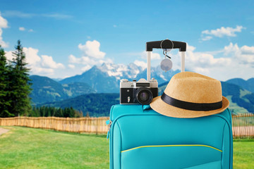 recreation image of traveler luggage, camera and fedora hat in front of a rural landscape. holiday...