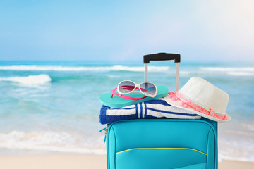 Wall Mural - holidays. travel concept. blue suitcase with female hat, flip flips, sunglasses and beach towel in front of tropical background