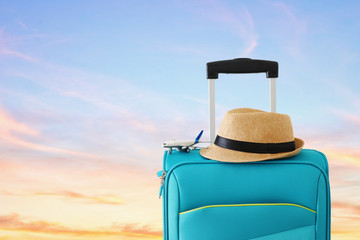 Wall Mural - holidays. travel concept. blue suitcase and airplane toy infront of sunset background