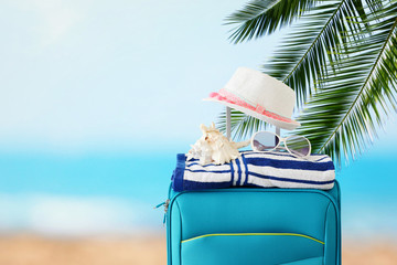 Wall Mural - holidays. travel concept. blue suitcase with female hat, sea shell, sunglasses and beach towel in front of tropical background