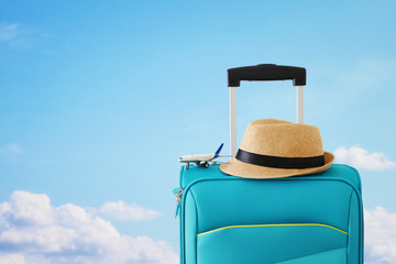 Wall Mural - holidays. travel concept. blue suitcase and airplane toy infront of sky background