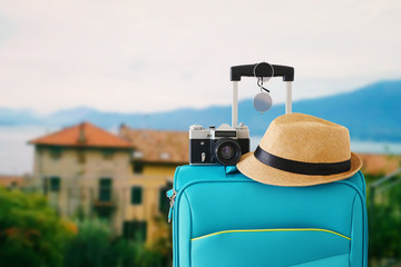 Wall Mural - recreation image of traveler luggage, camera and fedora hat in front of a rural landscape. holiday and vacation concept